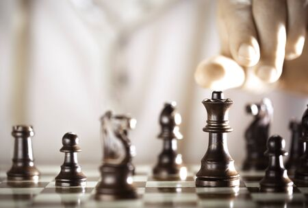 planning strategy: Board game, chess player hand about to play, excellence concept. Stock Photo