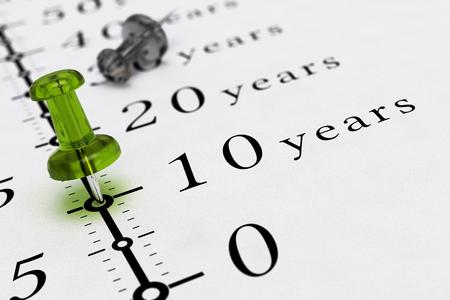 chronology: 10 a�os escritas en un papel con una imagen del concepto de chincheta azul, para la visi�n de negocio o largo plazo prospectivo. Foto de archivo