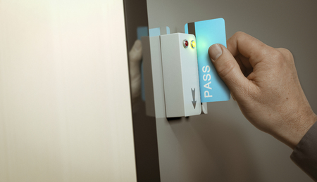 restricted: Hand with blue pass card unlocking access to a restricted area. Concept image for security and data protection. Stock Photo