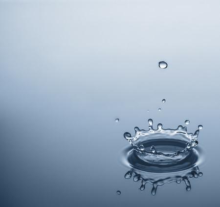 reflexion: Las gotas de agua que salpica un fondo azul claro con la reflexi�n y el espacio para el texto.