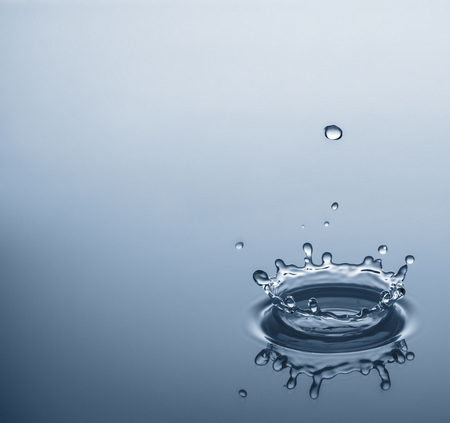 room for your text: Water drops splashing a clear blue background with reflexion and room for your text.