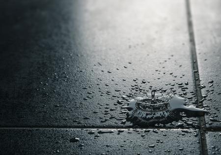 Wasser tropft fallen auf einem wasserbeständigen Fliesenboden. Schwarz und Blau-Töne mit Exemplar auf der linken Seite. Konzept der Wasseraustritt und Versicherung