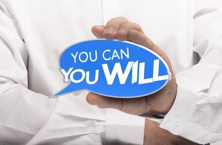 determination: Hand holding a bubble speech where it is written you can and you will. Motivational concept for determination and willpower. Stock Photo