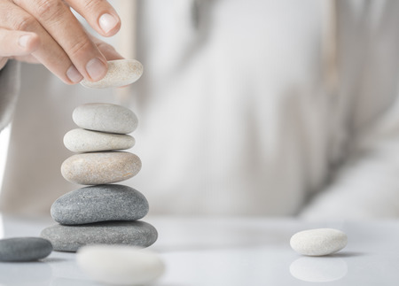 self development: Horizontal image of a man stacking pebbles on a table with copyspace for text. Concept of personal development or self realization.