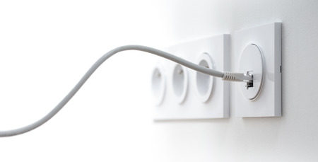 Close-up of an ethernet cable plugged into a wall socket, horizontal image with free space for text