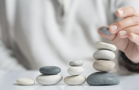 Horizontal image of a man stacking pebbles on a table with copyspace for text. Concept of risk management and wealth. Archivio Fotografico