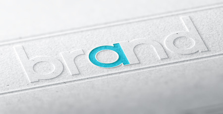 3D illustration of the word brand embossed on a paper background with blur effect. Concept of company brandname or corporate identity