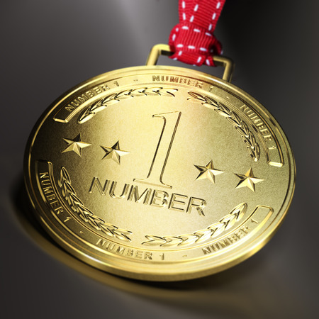 Golden medal with the text number one over dark background. Composite between an image and a 3D background. Concept of business or sport ambition. Stock Photo