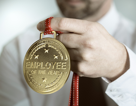 Employee holding golden medal with the text employee of the year. Incentive or motivation concept Archivio Fotografico