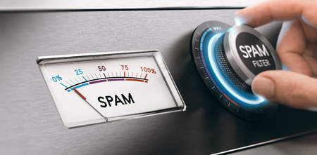 Conceptual image of spam filter, hand turning a knob to the maximum email filtering position. Concept of junk mail avoidance. Composite between an image and a 3D background. Stock Photo