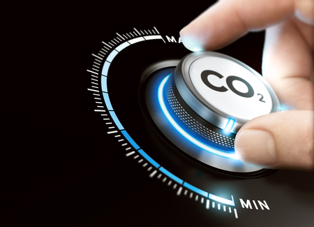 Man turning a carbon dioxyde knob to reduce emissions. CO2 reduction or removal concept. Composite image between a hand photography and a 3D background. Stockfoto
