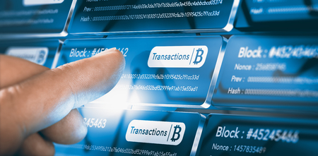 Finger pressing a blockchain block with the text transaction, a bitcoin symbol and security sha256 algorithm hach. Composite between a hand photography and a 3D background