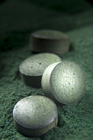 Close up of spirulina tablets on powder background with low depth of field. Vertical image.