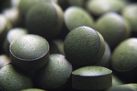 Close up of many spirulina tablets with low depth of field. Horizontal image.