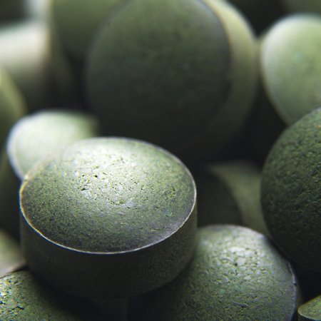 Blue green algae. Close up of natural organic spirulina tablets with focus at the foreground and blur effect