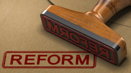 3D illustration of a rubber stamp with the word reform stamped on kraft paper envelope.