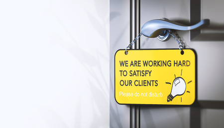 3D illustration of a door hanger with the text we are working hard for our clients, Concept of employee engagement for customer satisfaction. Stock Photo