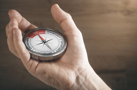 Man hand showing compass with needle pointing the text best opportunity. Concept image to illustrate business or career opportunities. Imagens