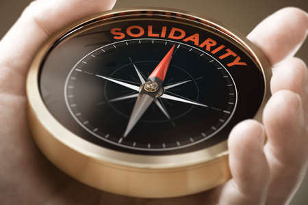Man hand holding compass with needle pointing the word solidarity. Sociology concept. Composite image between a hand photography and a 3D background. Imagens