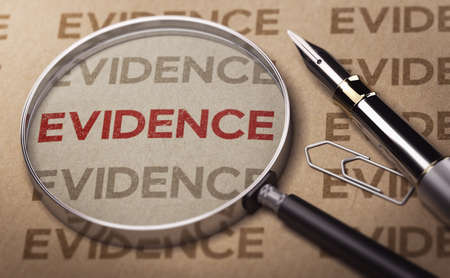 Magnifying glass over the word evidence written on a sheet of paper.