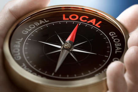 Hand holding a compass with needle pointing the word local. Consumption concept. Composite image between a hand photography and a 3D background.