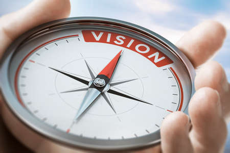 Hand holding a compass with needle pointing the word vision. Company or organization Statement values. Composite image between a hand photography and a 3D background. Imagens