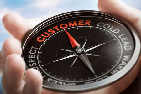Hand holding a compass with needle pointing the word customer. Acquisition concept. Composite image between a hand photography and a 3D background.