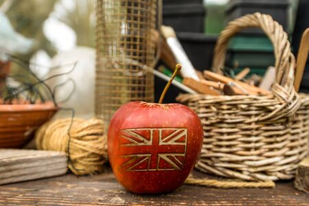 An apple with a British union jack flag on in an English garden