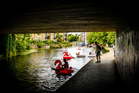 London/UK - 9/8/20 - A group of friends playing on inflatables in the canal