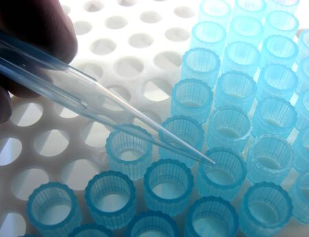 Scientist hand using a pipette in a research lab