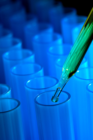Pipette over blue test tubes Stock Photo