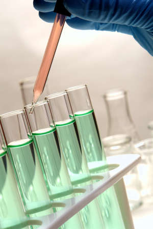 drug discovery: Scientist hand using a pipette over test tubes in a research lab Stock Photo