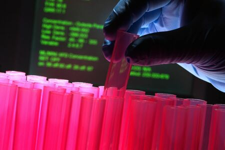 Scientist hand working with pink test tubes with scientific monitor background