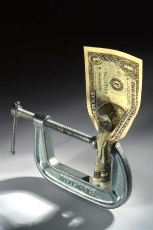 Single Dollar bill crushed in an adjustable clamp