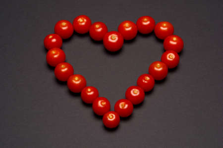 Heart shaped with cherry tomatoes over dark grey background photo