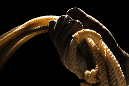 hondo: Cowboy hand with glove holding a rodeo lasso