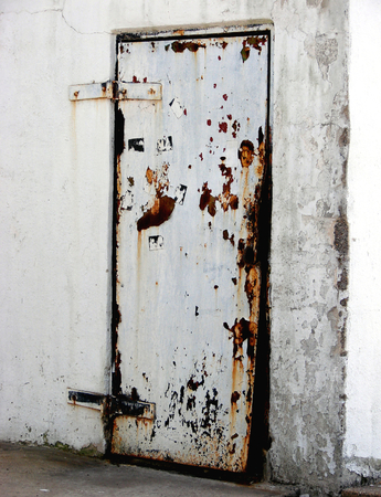 industry: Rusty metal door on an abandoned industrial building