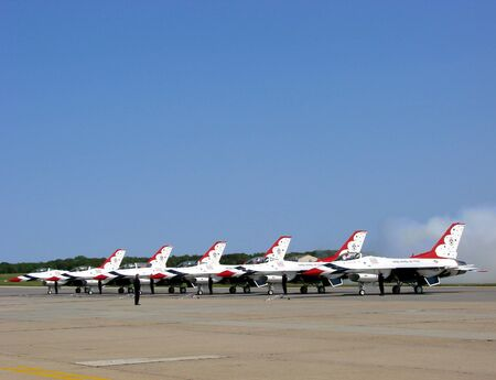 lockheed martin: USAF Thunderbirds lined up on the ground reving engines with plume of smoke
