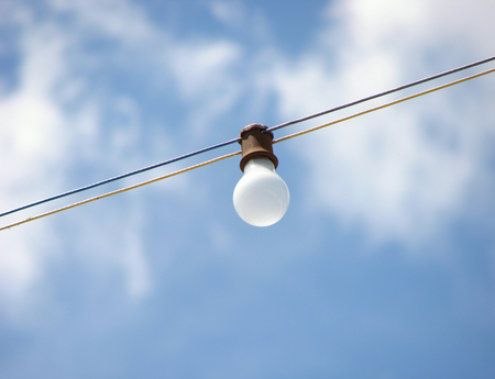 Single light bulb on a string over blue sky