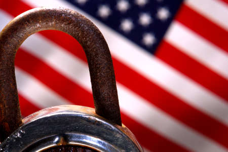 spangled: Rusty padlock in front of an American flag
