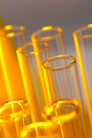 Glass test tubes with amber glow in a research lab