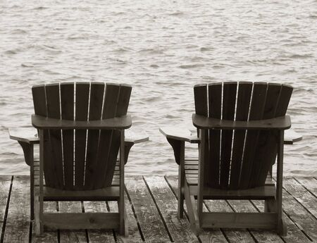 Adirondack chairs on a wooden dock facing the sea photo
