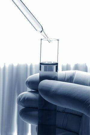 Scientist hand die een reageerbuis met pipet hierboven in een experiment Stockfoto