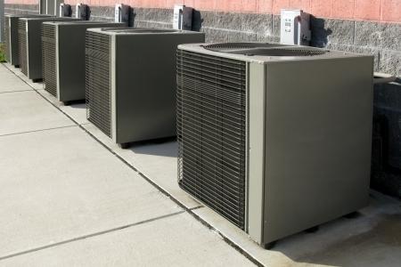 Rij van commerciële airco compressor eenheden de buurt van een industrieel gebouw