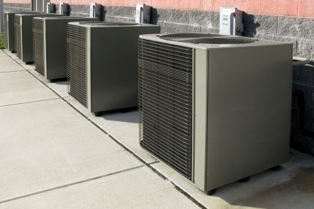 air: Row of commercial air conditioner compressor units near an industrial building