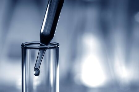 Glass pipette with emerging drop in a glass test tube in a research lab in blue tone color photo