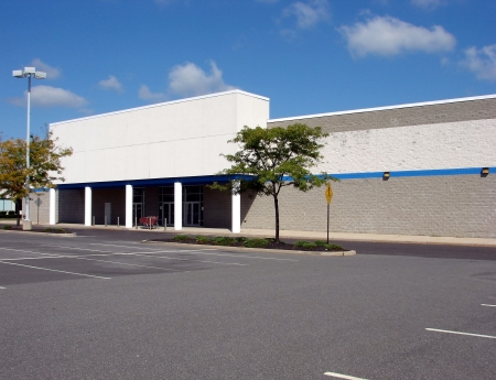store: Front entrance and parking of an empty big box retail store