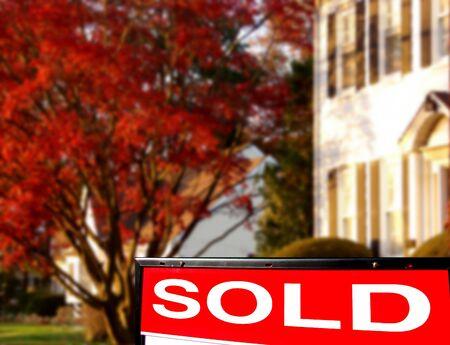 listing: Las propiedades inmobiliarias vendieron la muestra delante de una casa blanca Foto de archivo