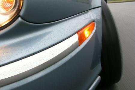 Speeding car in rain with turn signal flashing with true road motion blur
