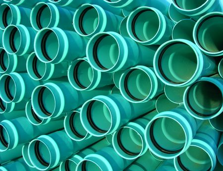 Pile of new green pvc sewer pipes on construction site